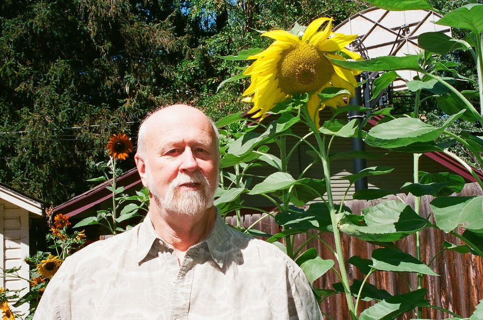 Tom Trusky next to the sunflowers he grew in his backyard in Boise Idaho in 2008. Photo by Enver Sulejman