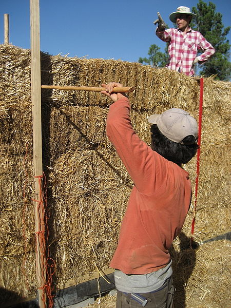 Building a straw-bale house. Source philipp/Wikimedia Commons